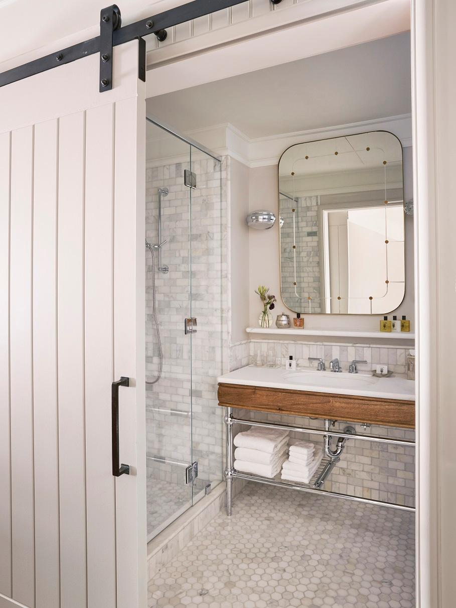 Carrara marble-tiled bathroom with state-of-the-art over sized rain shower