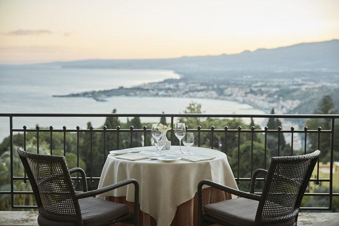 Taste authentic Sicilian dishes while admiring the Bay of Taormina and Mount Etna